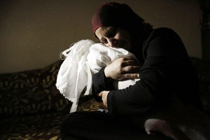 巴勒斯坦婦人Netream Netzleam抱著她死去的女兒。她的女兒死於7月18日的空襲,今年1歲。