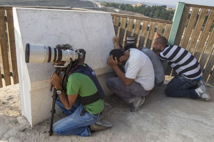 以色列的記者與居民正在山上看雙方的戰鬥。
