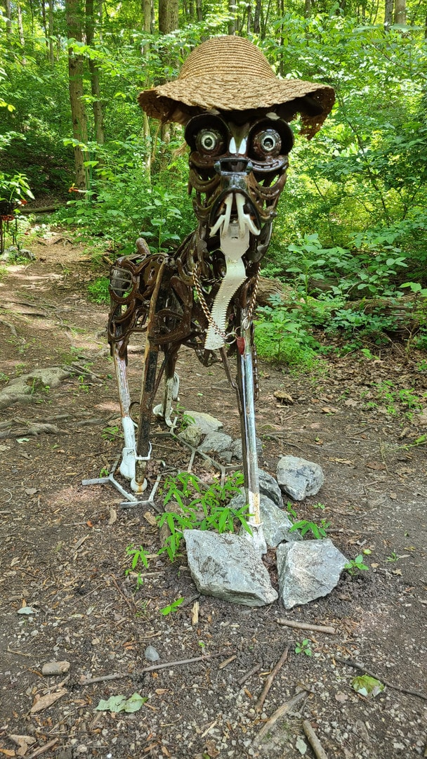 A dog made out of scrap metal is wearing a floppy hat