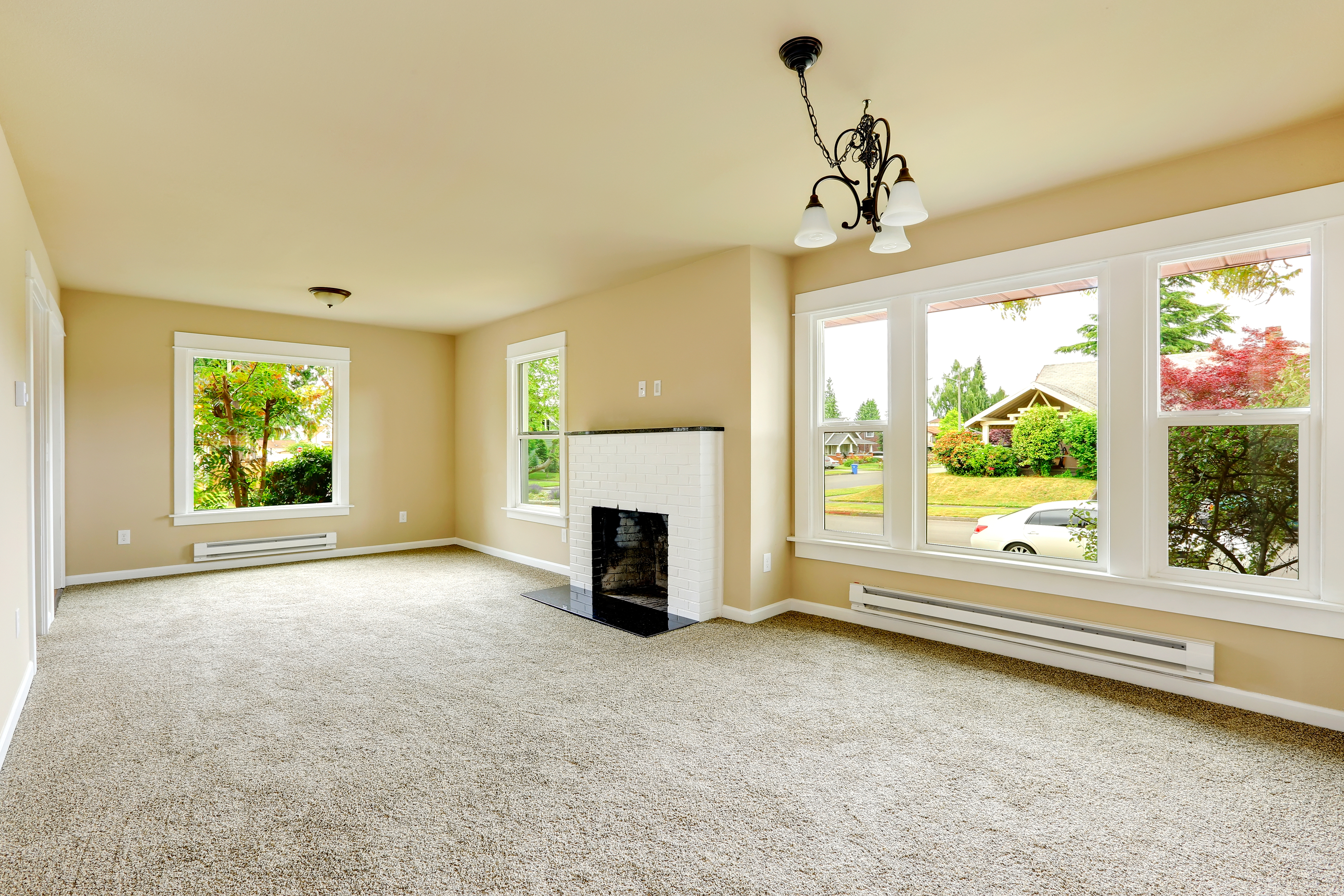Emtpy house interior. Family room with ivory walls and light grey carpet floor. Room has white brick background fireplace