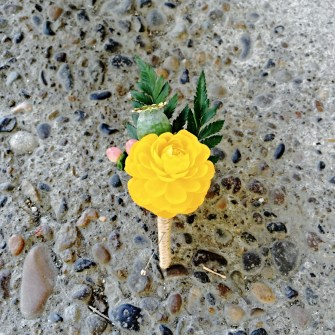yellow ranunculus with pods & berries boutonniere