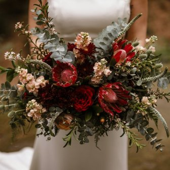 Boho bouquet with proteas in muted red, burgundy and blush