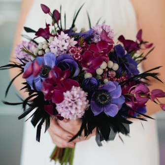 Exotic purple bridal bouquet with black feathers