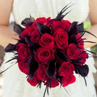 red roses & black calla lilies with feathers