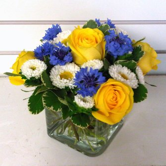 mixed flowers in a low small cube arrangement in yellow, white, and blue