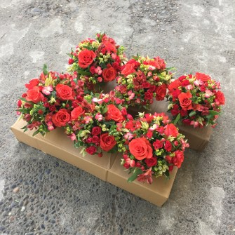 custom red and terracotta colored centerpieces for a private dinner party