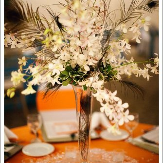white dendrobium orchids peacock feathers in tall wedding centerpiece