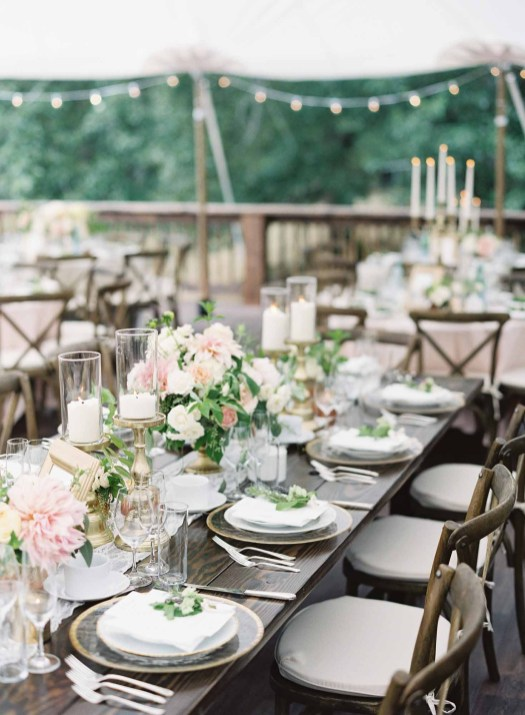 Long wooden table filled with flowers and candles at large tent wedding - designed by Flora Nova Design