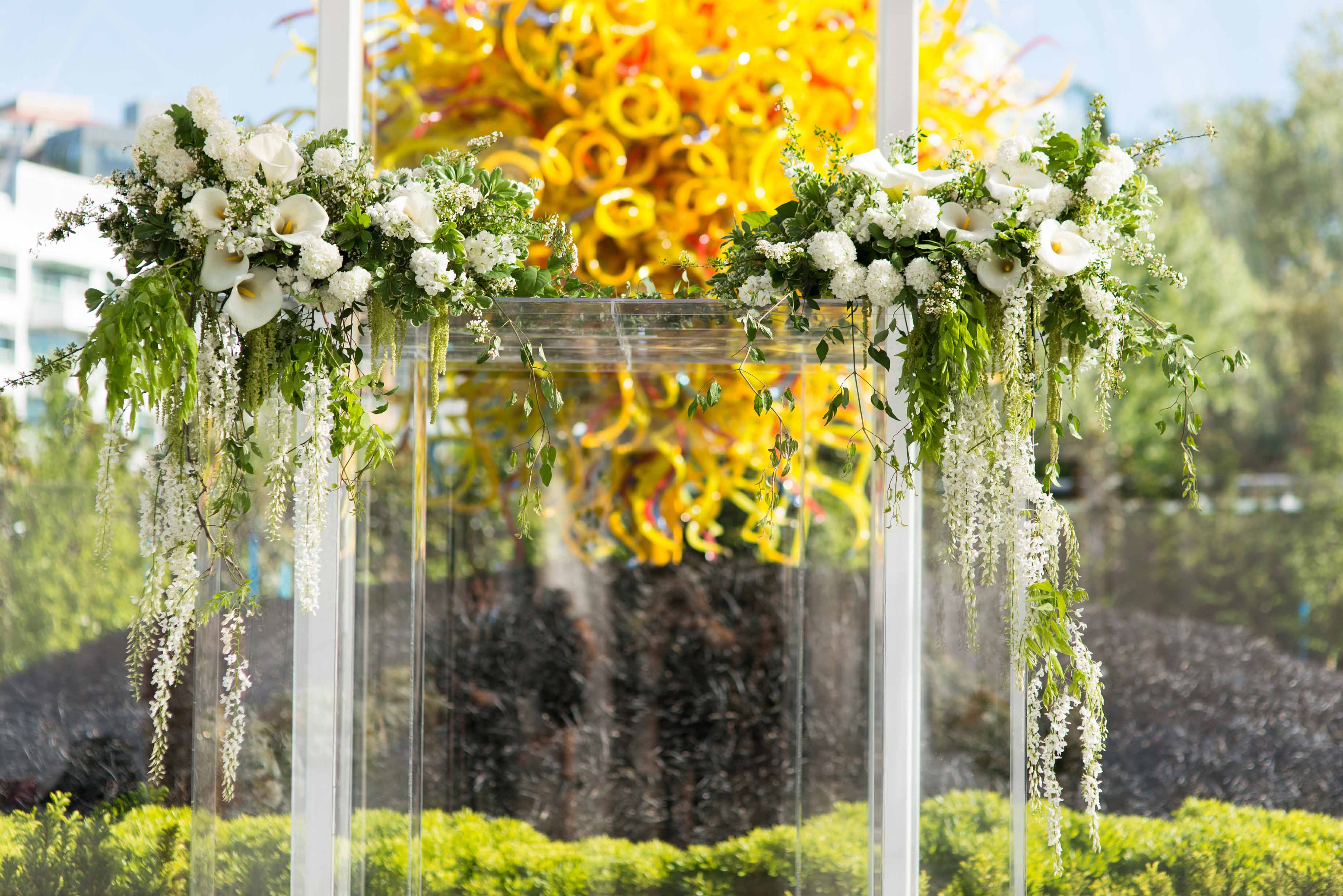 Clear lucite wedding chuppah covered in greenery and white spring flowers with large Chihuly glass sun in background