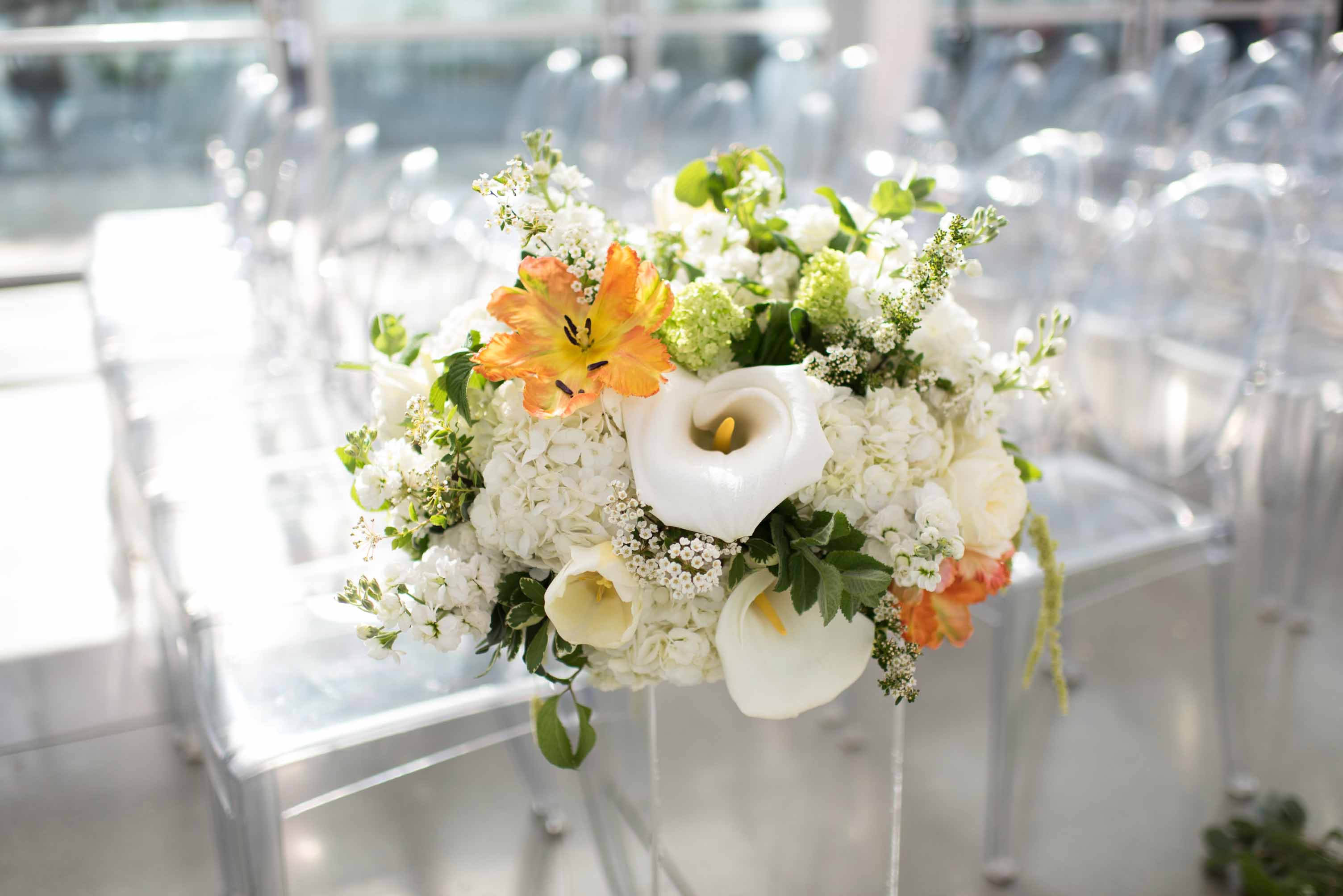 Beautiful white and orange floral design with large white calla lilies, white roses, viburnum, blooming spirea, and parrot tulips on top of lucite pedestals and lucite wedding ceremony chairs