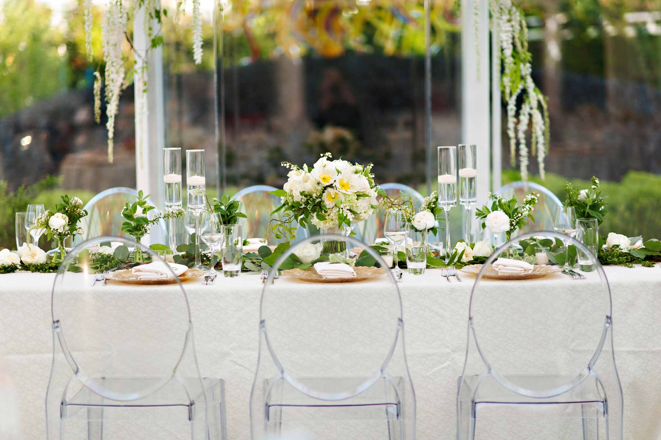 Wedding head table lined with greenery and spring flowers with clear ghost chairs