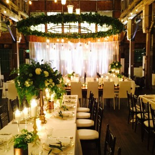 Long white reception tables, with tall greenery centerpieces, black Chivari chairs, and large ceiling greenery wreath - Sodo Park Wedding - designed by Flora Nova Design Seattle