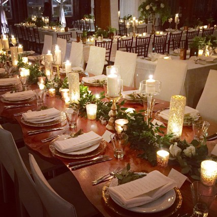 Long wooden table lined with gold candle holders, greenery garland, and votive candles - Sodo Park Wedding - designed by Flora Nova Design Seattle