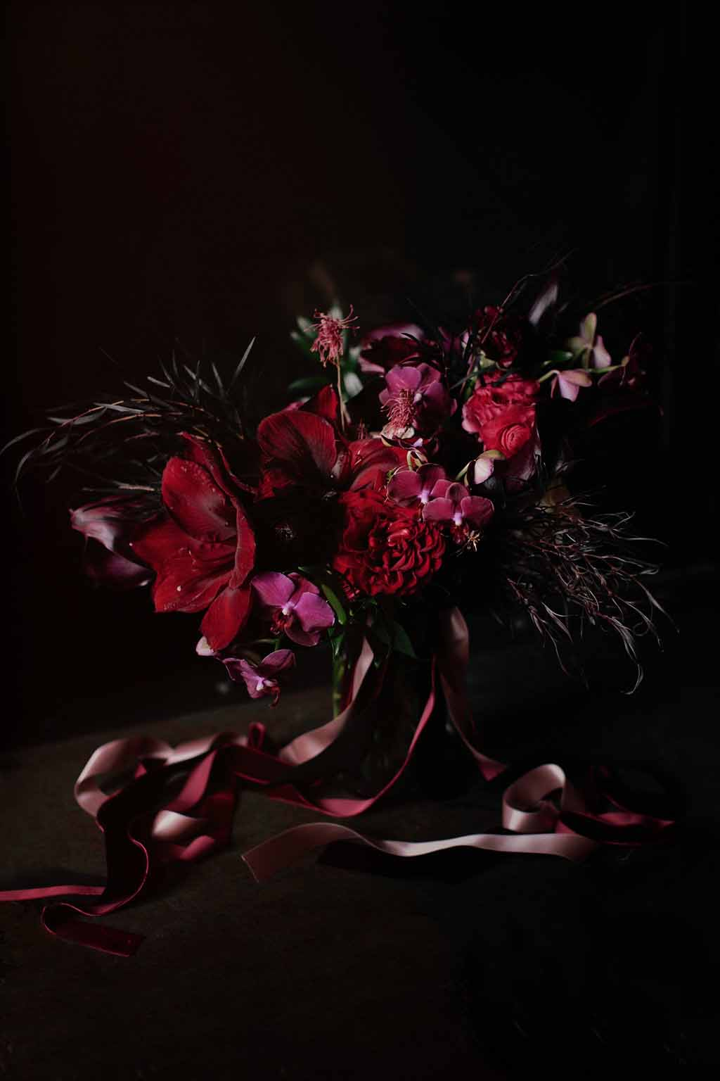 Oblong bouquet in deep red with red amaryllis, red garden roses, red ranunculus, and black agonis foliage, with long ribbon streamers - Bridal Bouquet Shapes by Flora Nova Design Seattle