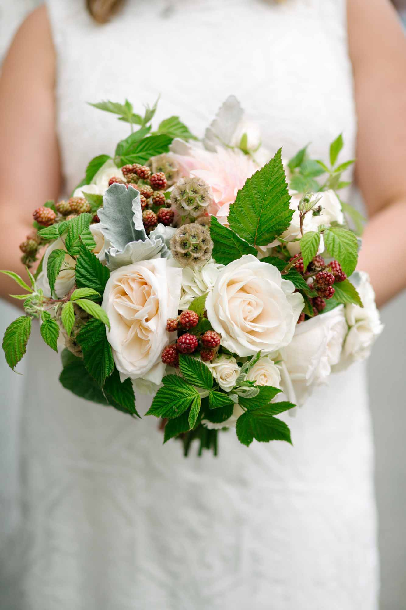 Textured bridal bouquet of ivory roses, scabiosa pods, hypericum berries, raspberry foliage - by Flora Nova Design Seattle