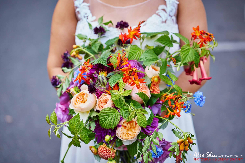 Lush garden-style bridal bouquet of Juliet garden roses, orange and blue garden flowers with raspberry foliage
