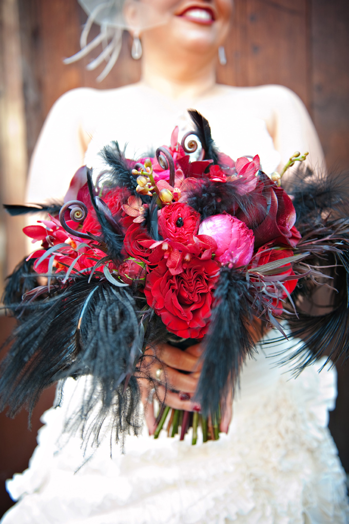 Halloween bridal bouquet of red and dark pink roses, with fiddle head fern curls, and black feathers