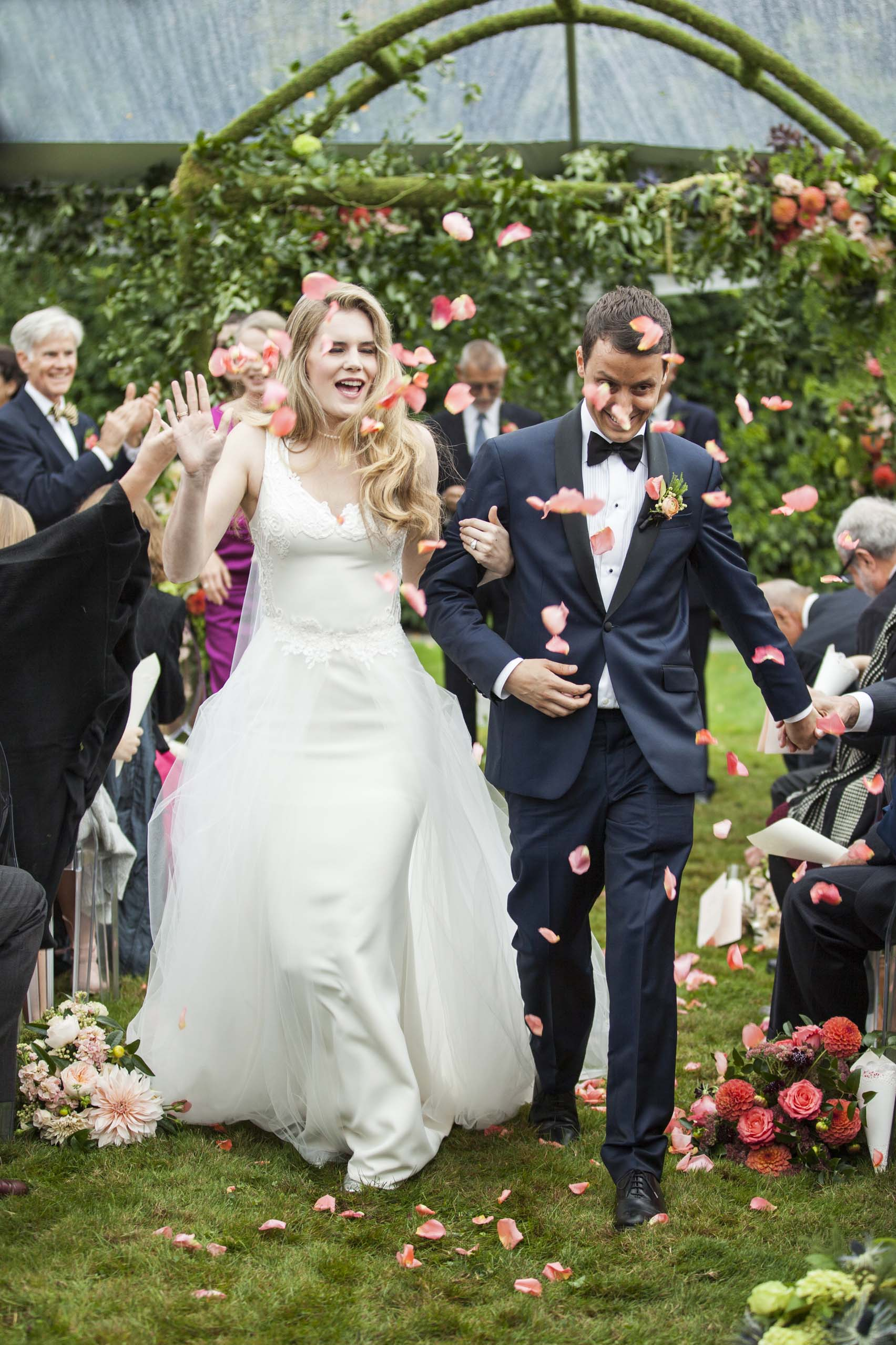 Bride and groom walking down aisle showered in rose petals at Pacific Northwest wedding