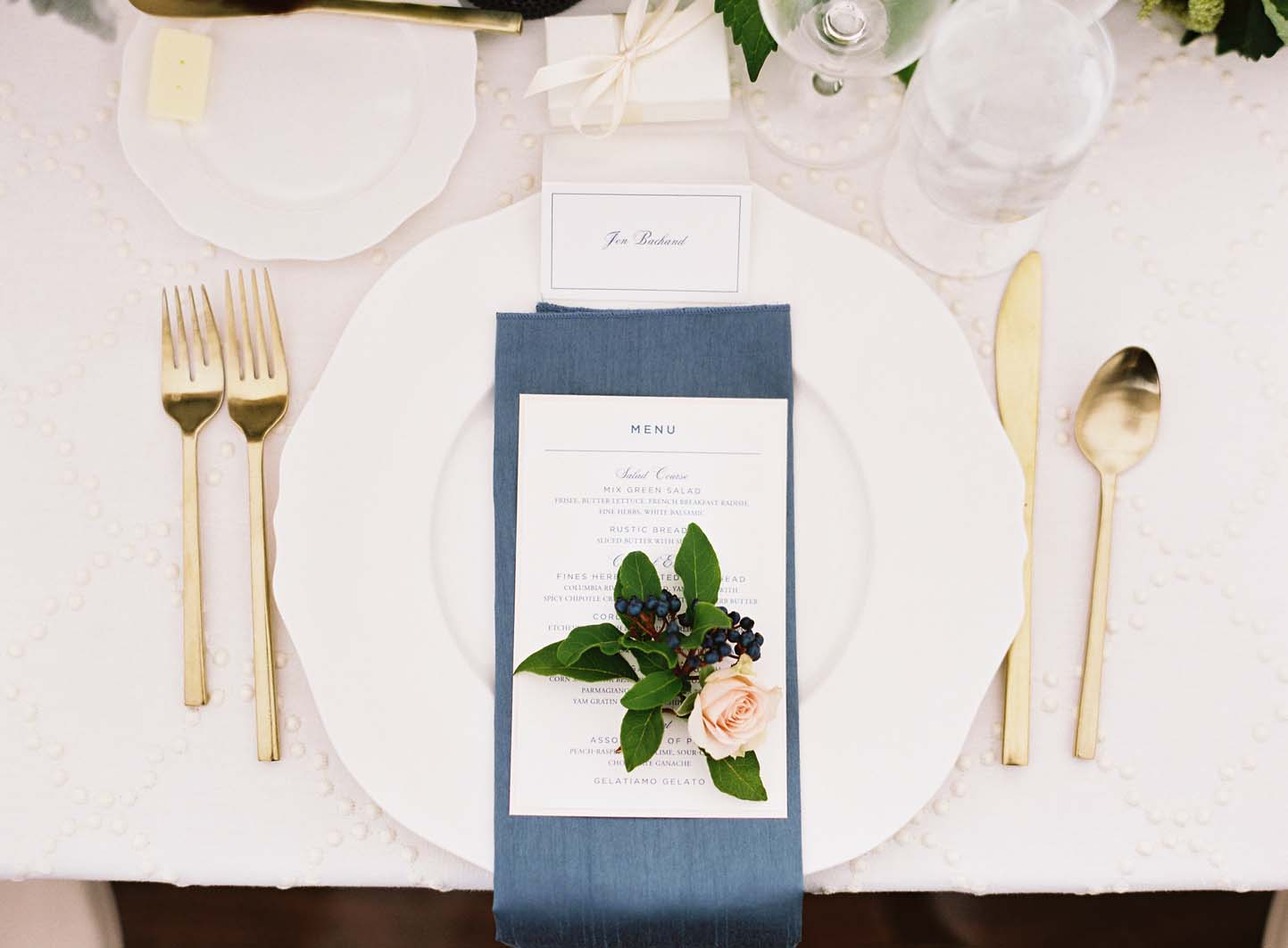 Place setting with French blue napkin, peach rose, and greenery treatment