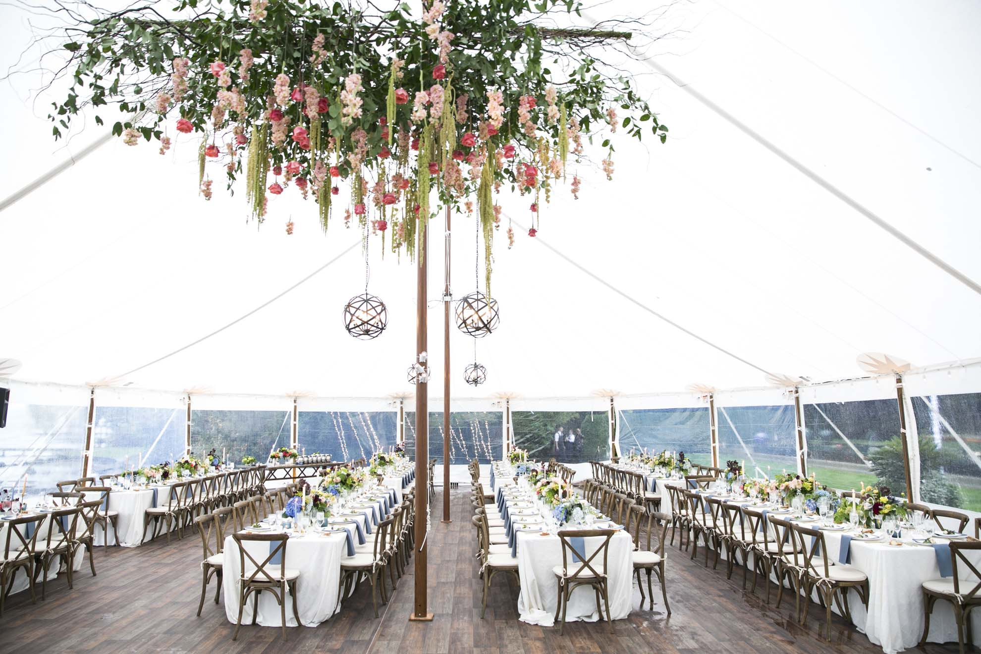Wedding tent with large floral chandelier above dance floor  with long reception tables and Vineyard chairs