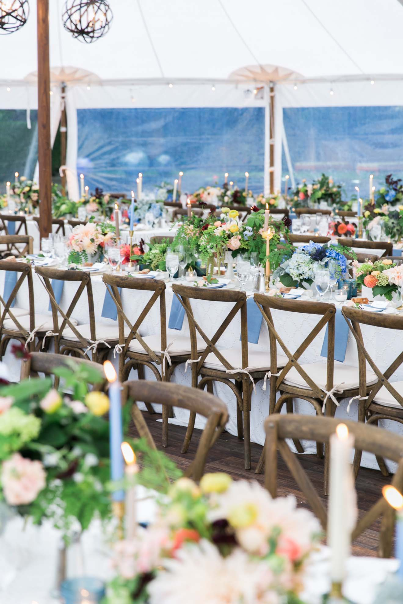 Tent wedding with long tables and vineyard chairs, orange and blue centerpieces at Pacific Northwest wedding designed by Flora Nova Design
