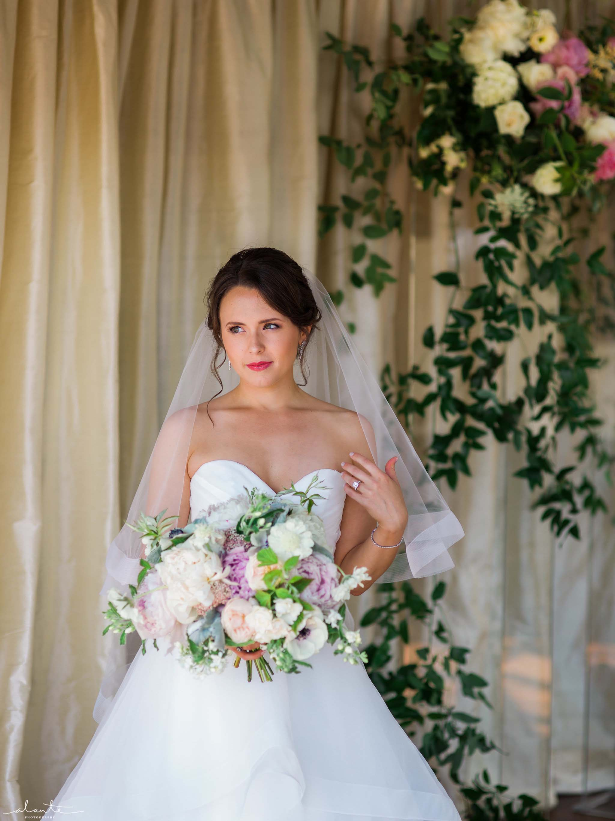 Bride with peony bouquet in front of greenery covered arboc, Olympic Rooftop Pavilion wedding with pink peonies by Flora Nova Design Seattle