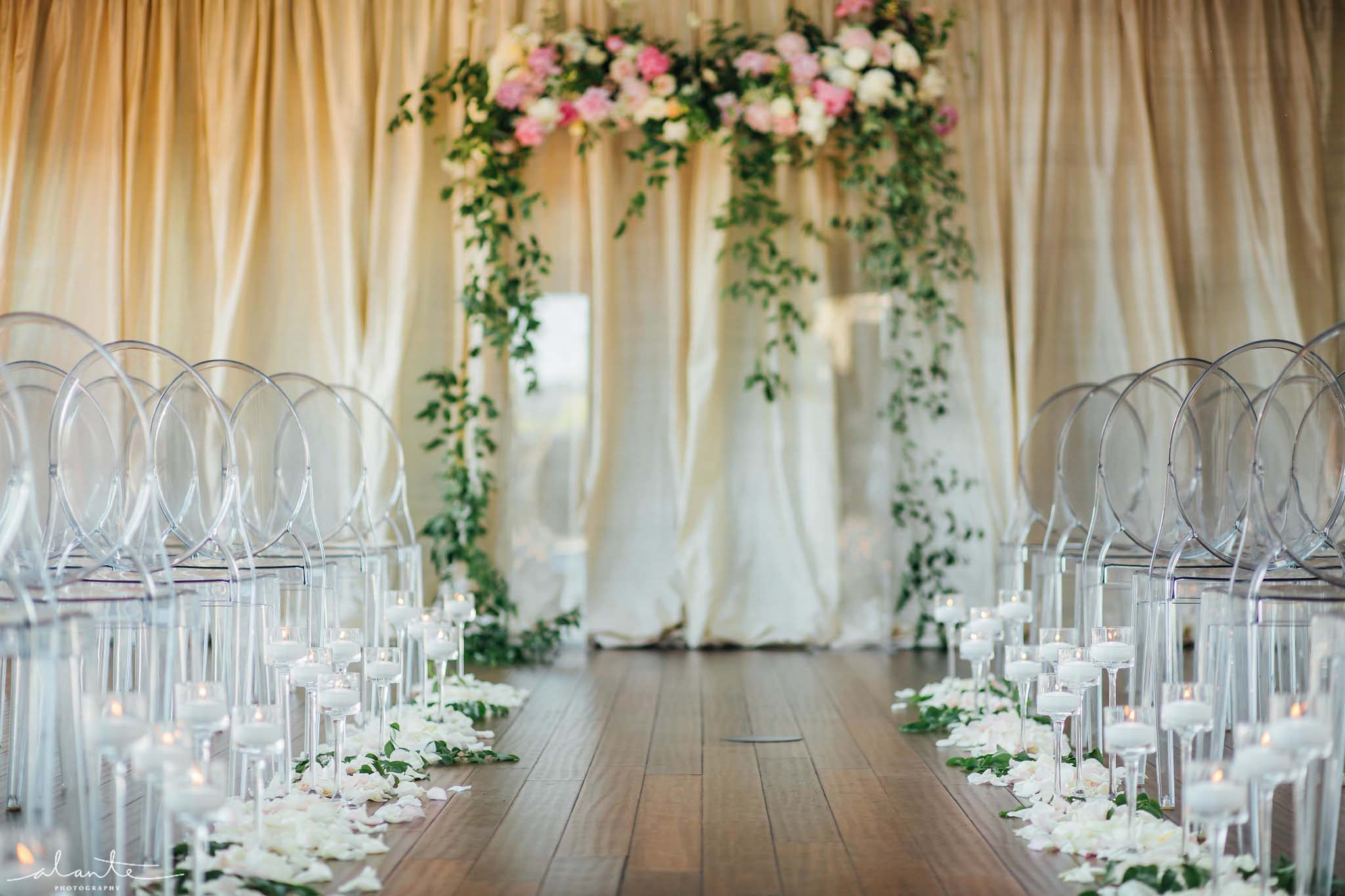 Lucite wedding arch covered in greenery and blush flowers with clear lucite chairs and candles lining the aisle - Olympic Rooftop Pavilion wedding with pink peonies by Flora Nova Design Seattle