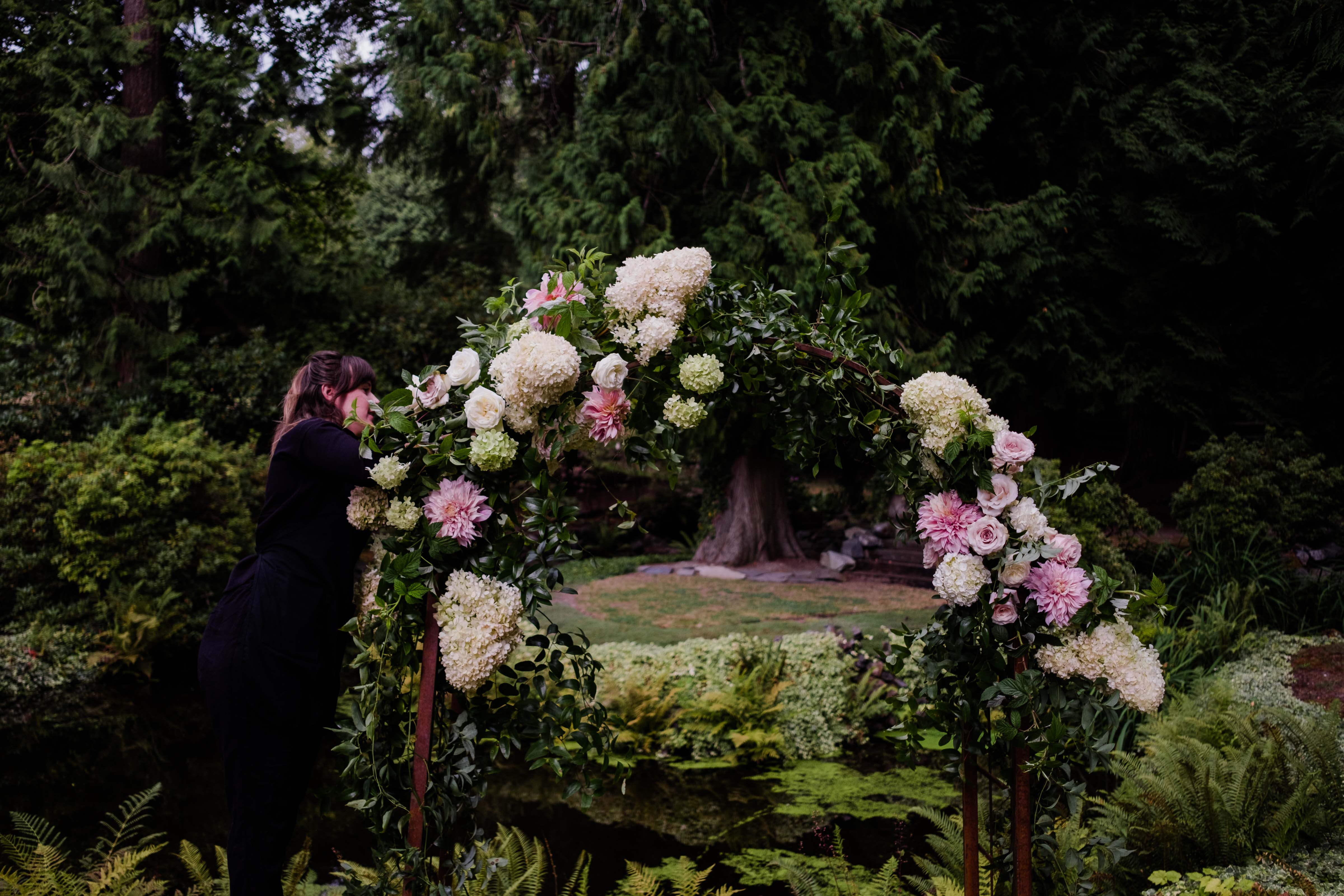 Designer adding the last touch to wedding arch - A Luxe Chateau Lill Wedding designed by Flora Nova Design Seattle