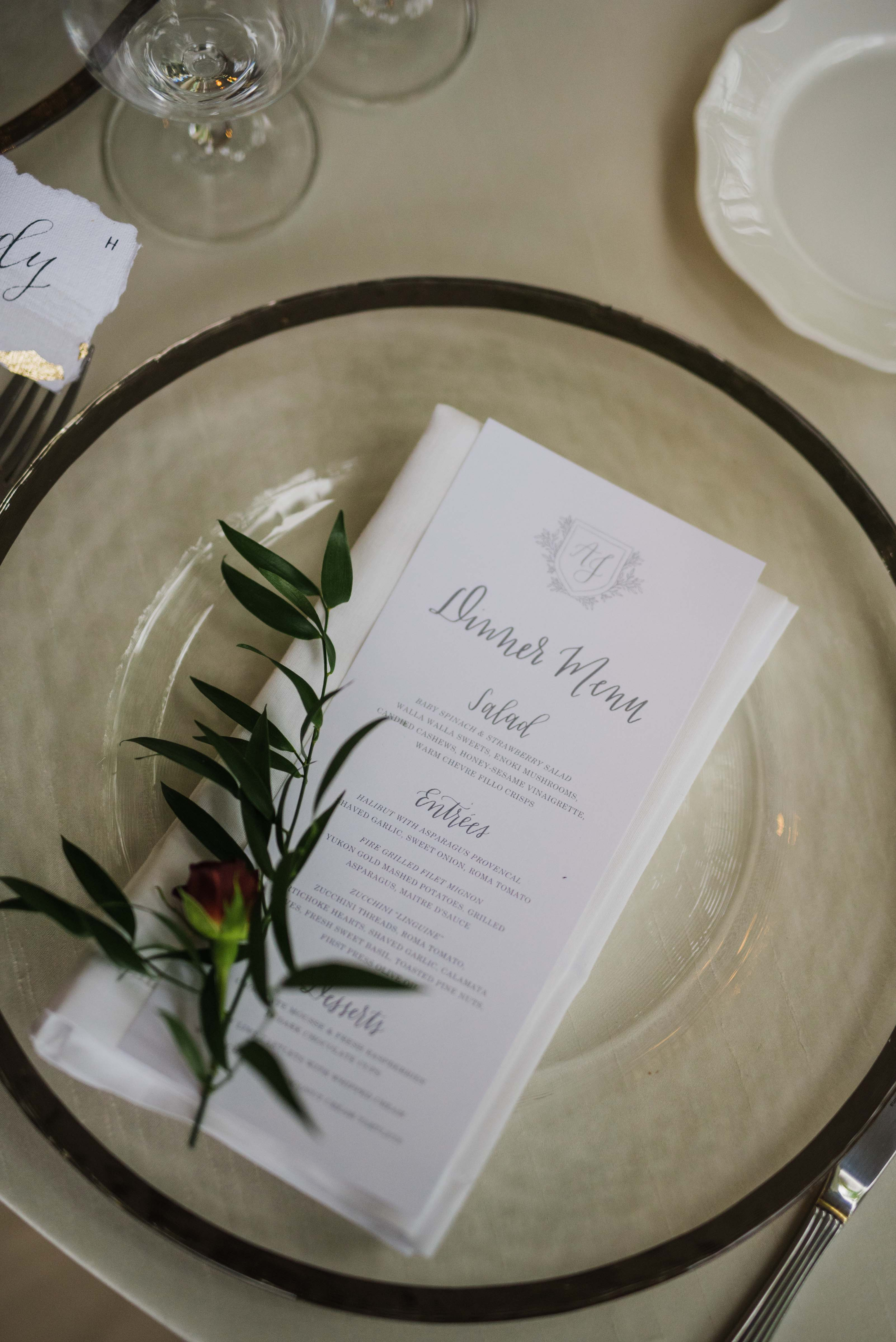 table setting with charger plate, menu, and greenery