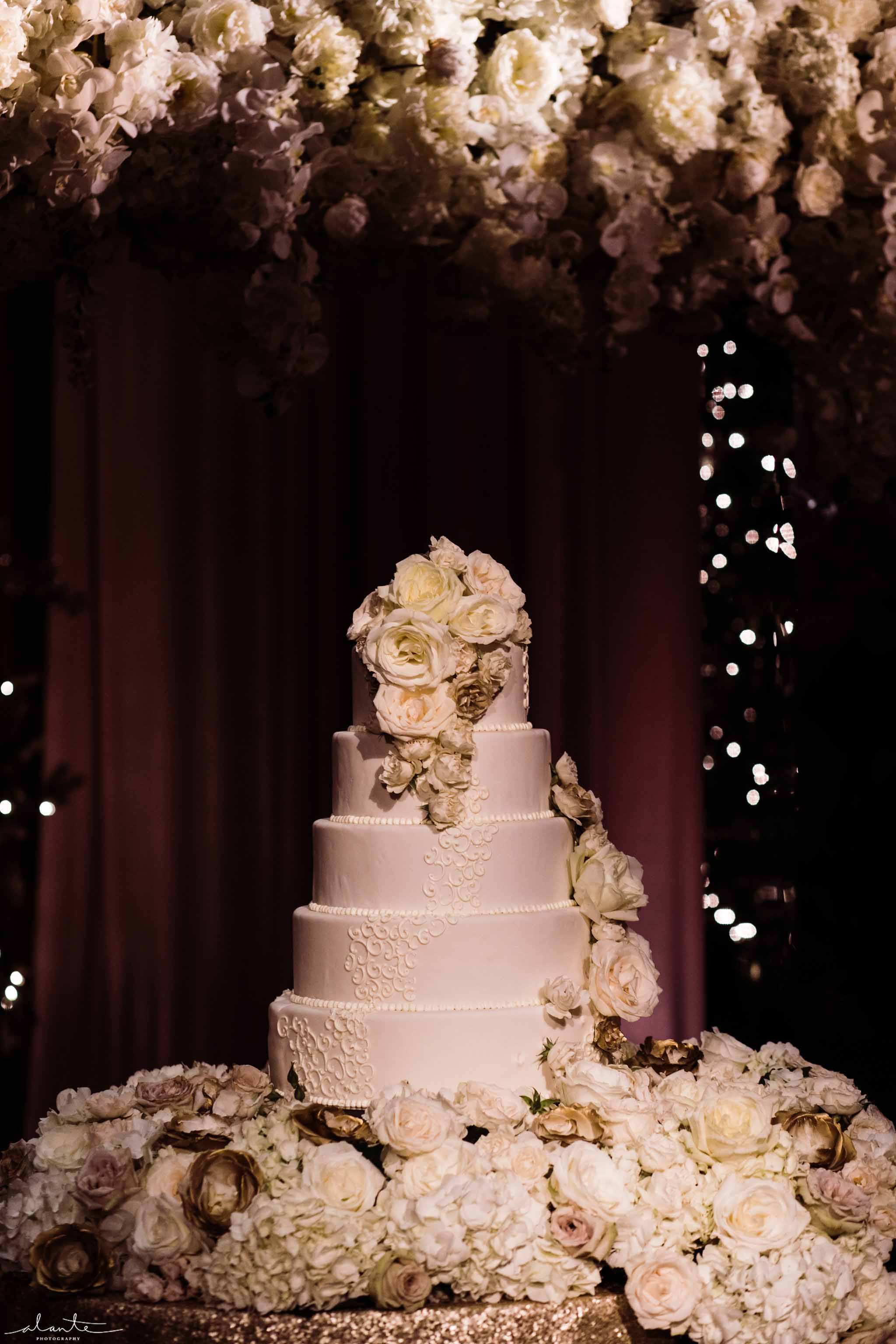 tall white wedding cake with flower arch