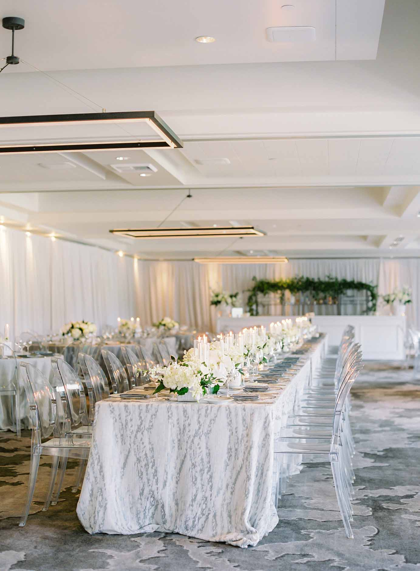 Long wedding guest table with light grey linen, clear lucite chairs at Overlake Country Club Wedding - by Flora Nova Design Seattle