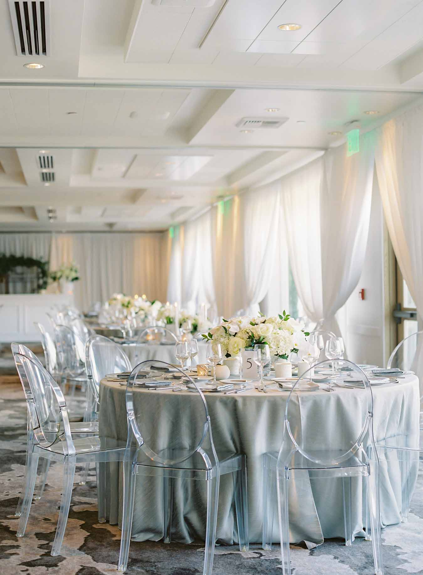 Round wedding tables, silver linens, clear lucite ghost chairs, with white flower centerpieces at Overlake Country Club Wedding