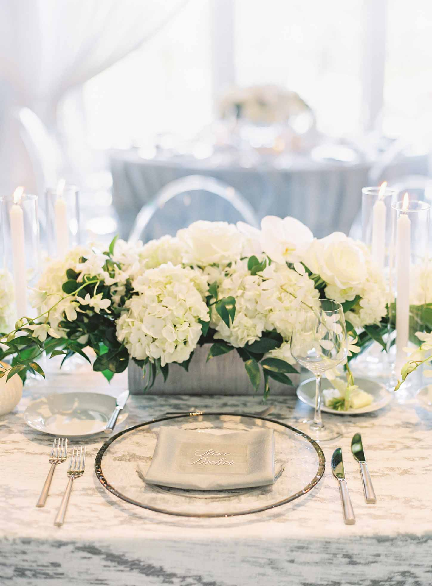 Centerpiece of white flowers with greenery in silver vase, a silver rimmed glass charher plate, clear lucite chairs - White and Green Wedding - by Flora Nova Design