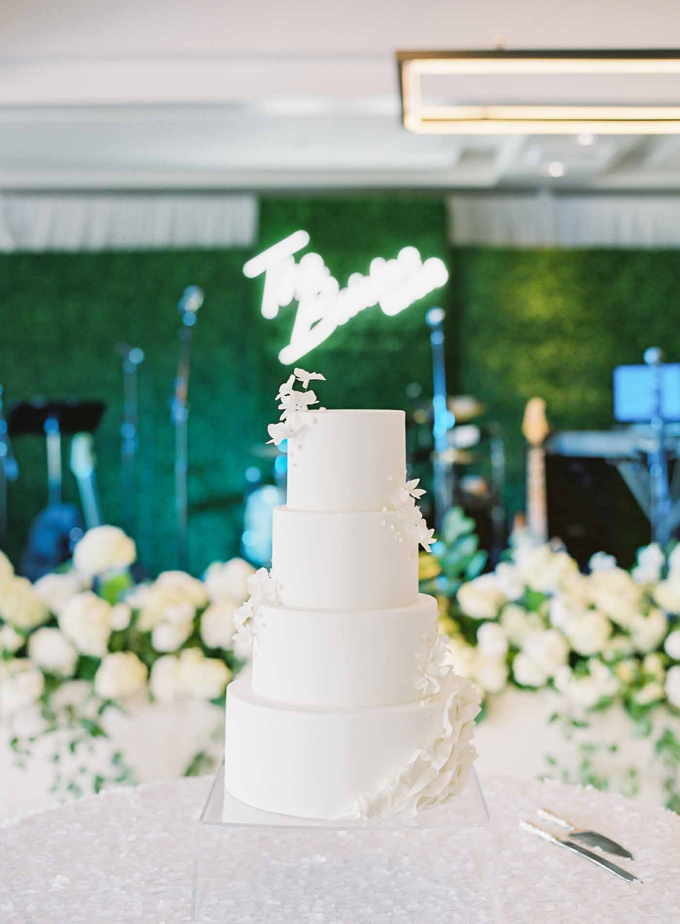 A White wedding cake on the dance floor in front of the decorated band backdrop with custom wedding signage