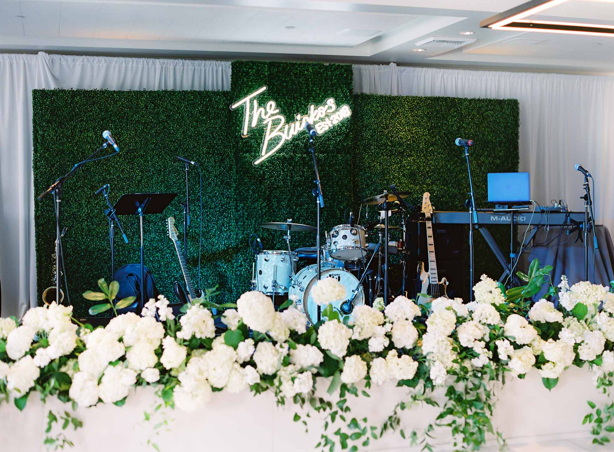Tall greenery wall, planters of white hydrangea, and a custom wedding sign was decor for the band stage - White and Green Wedding - Flora Nova Design