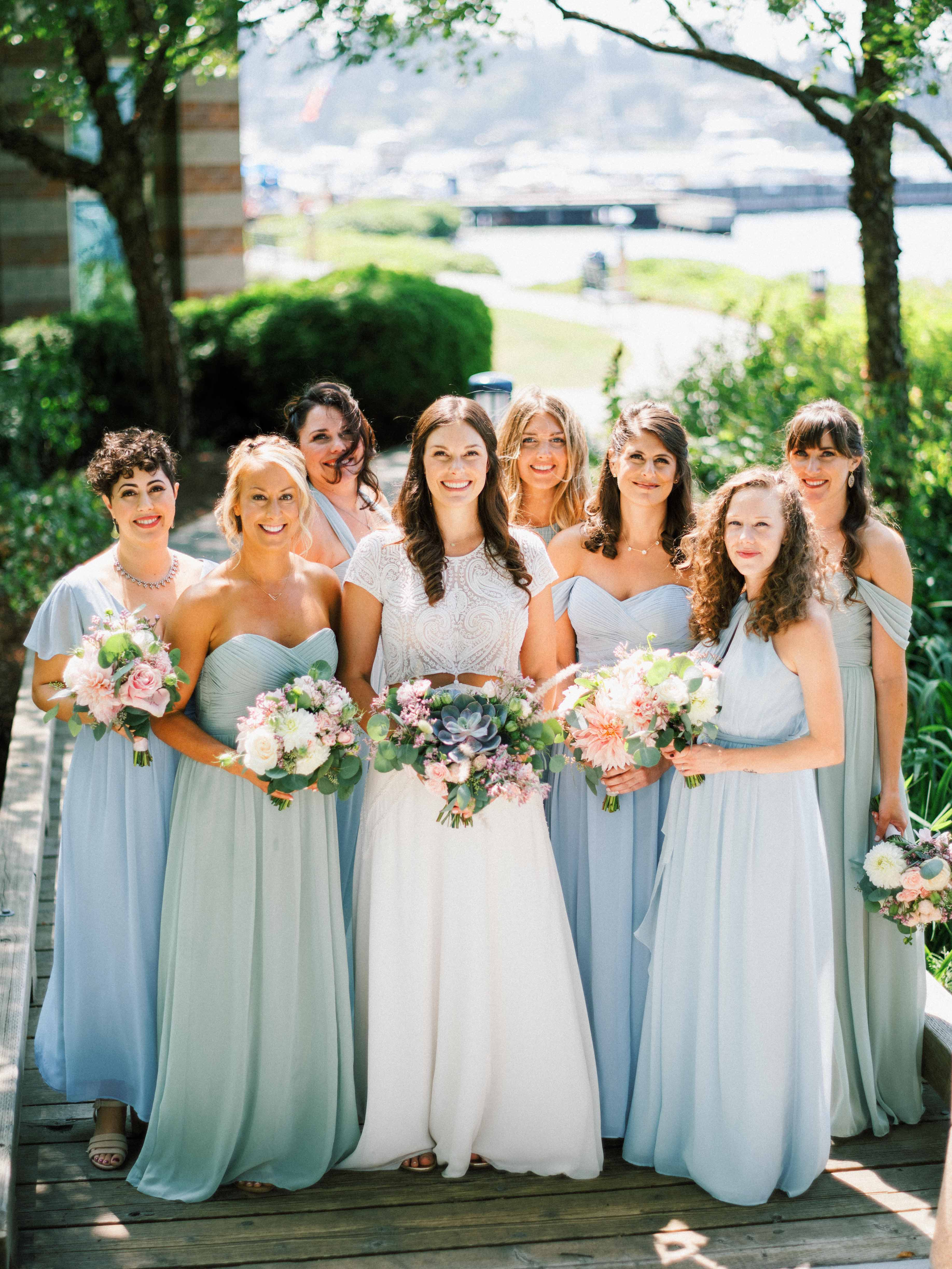 bridal party in blue green dresses holding bouquets of greenery and succulents - Woodmark Hotel Wedding by Flora Nova Design Seattle