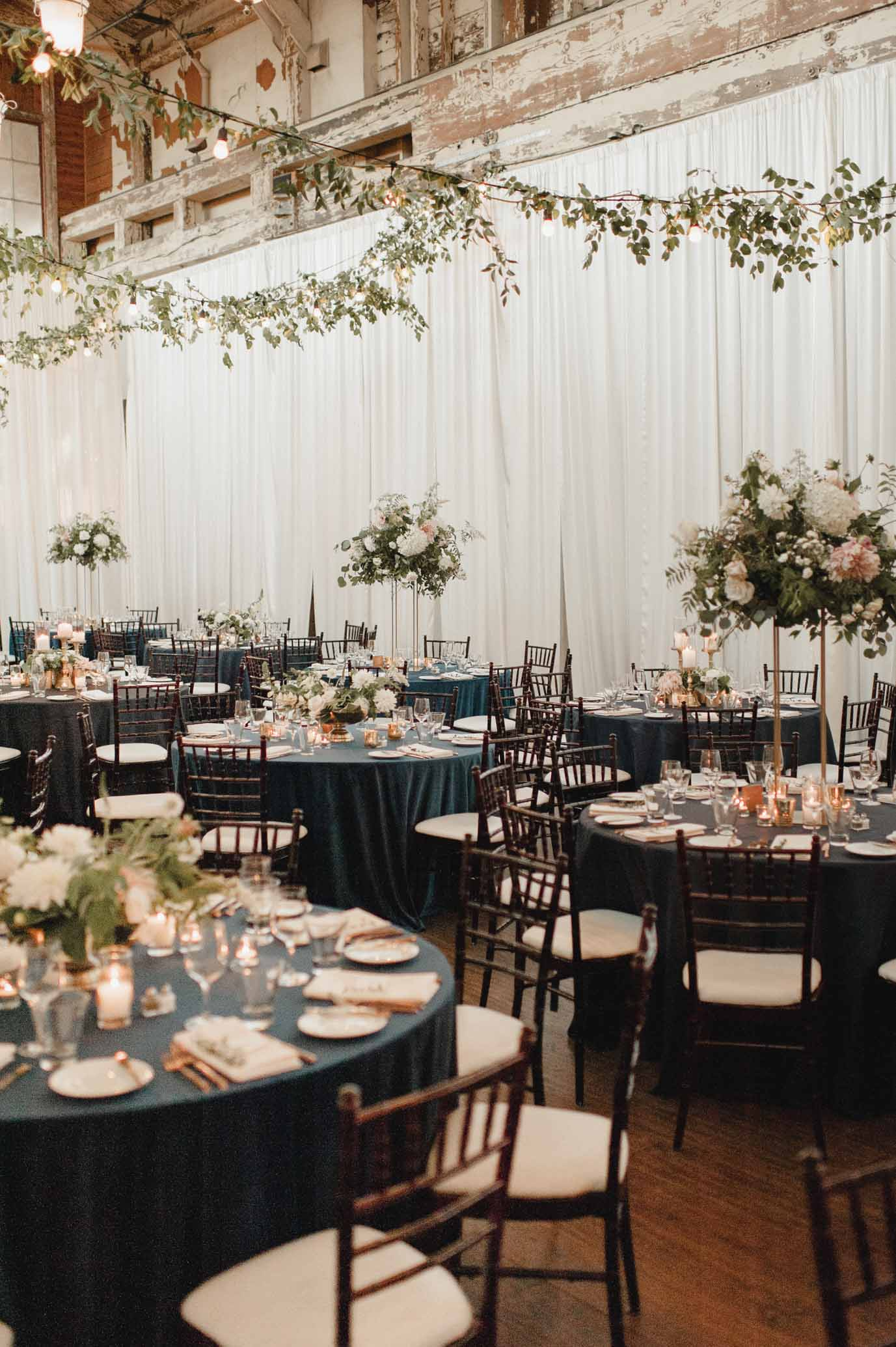 Wedding reception tables with blue linens, and greenery centerpieces - by Flora Nova Design Seattle