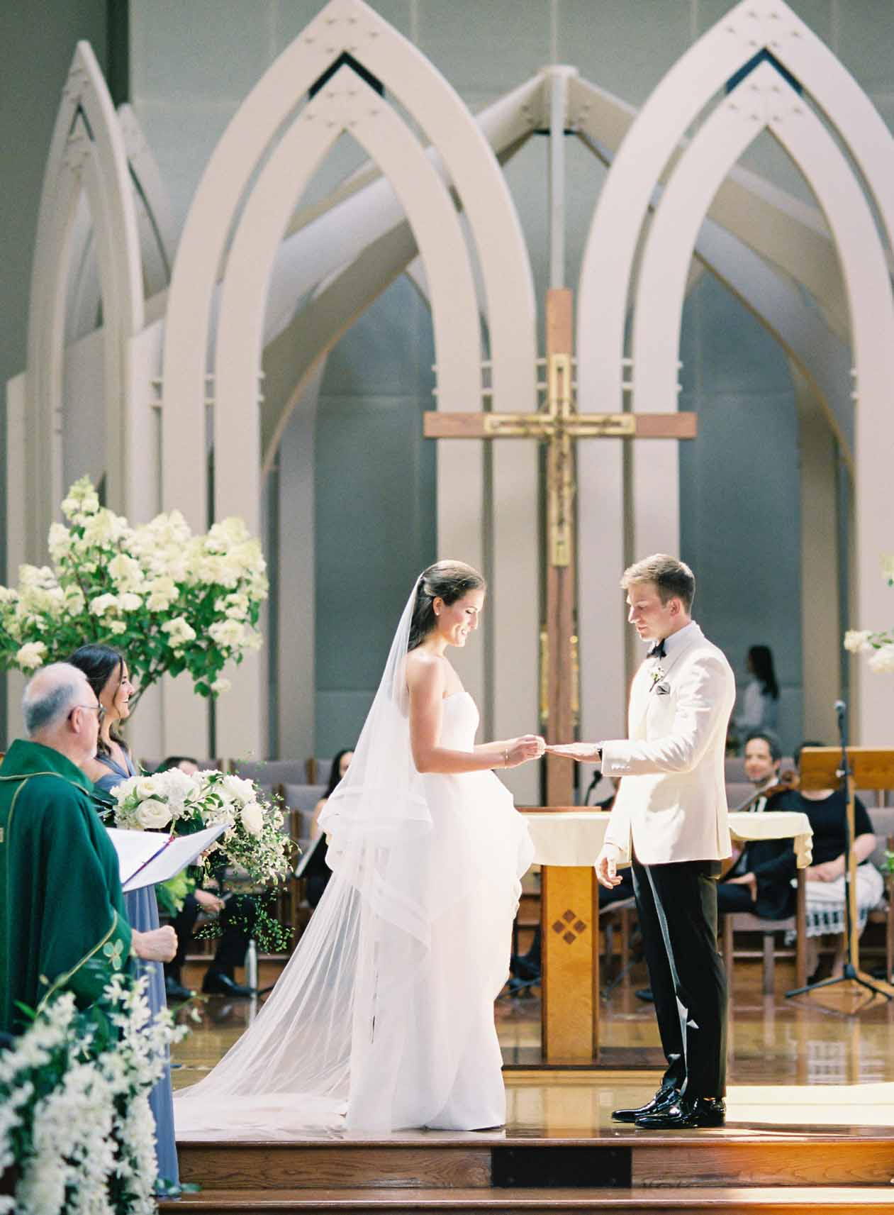 Wedding couple giving vows at church altar, with tall white hydrangea decorations