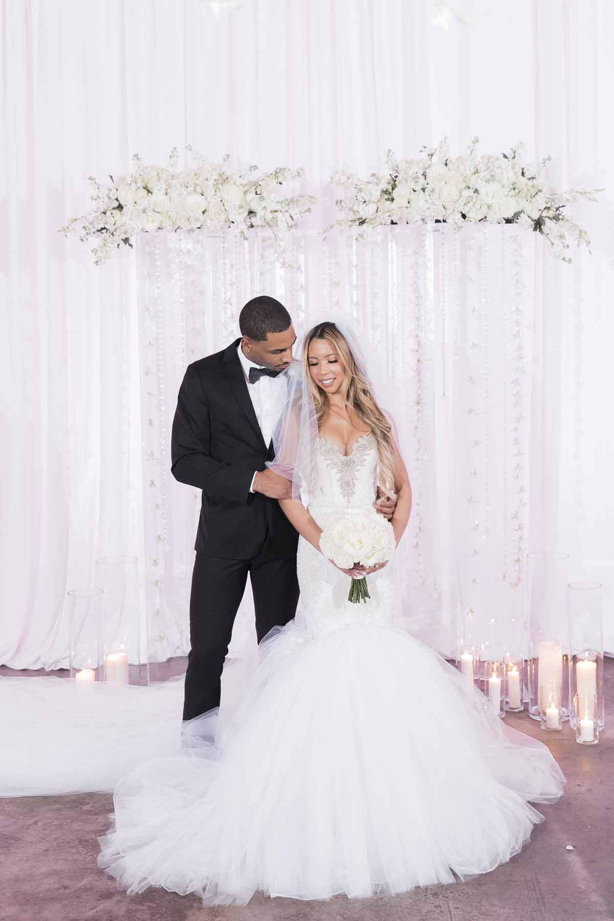 Bride and groom in front of their modern clear lucite wedding arch with white flowers