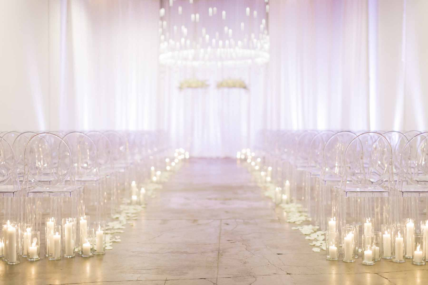 Wedding ceremony aisle in all white, lined with 100s of candles, crystal chandelier, white draping, flower arch, at Canvas Event space wedding