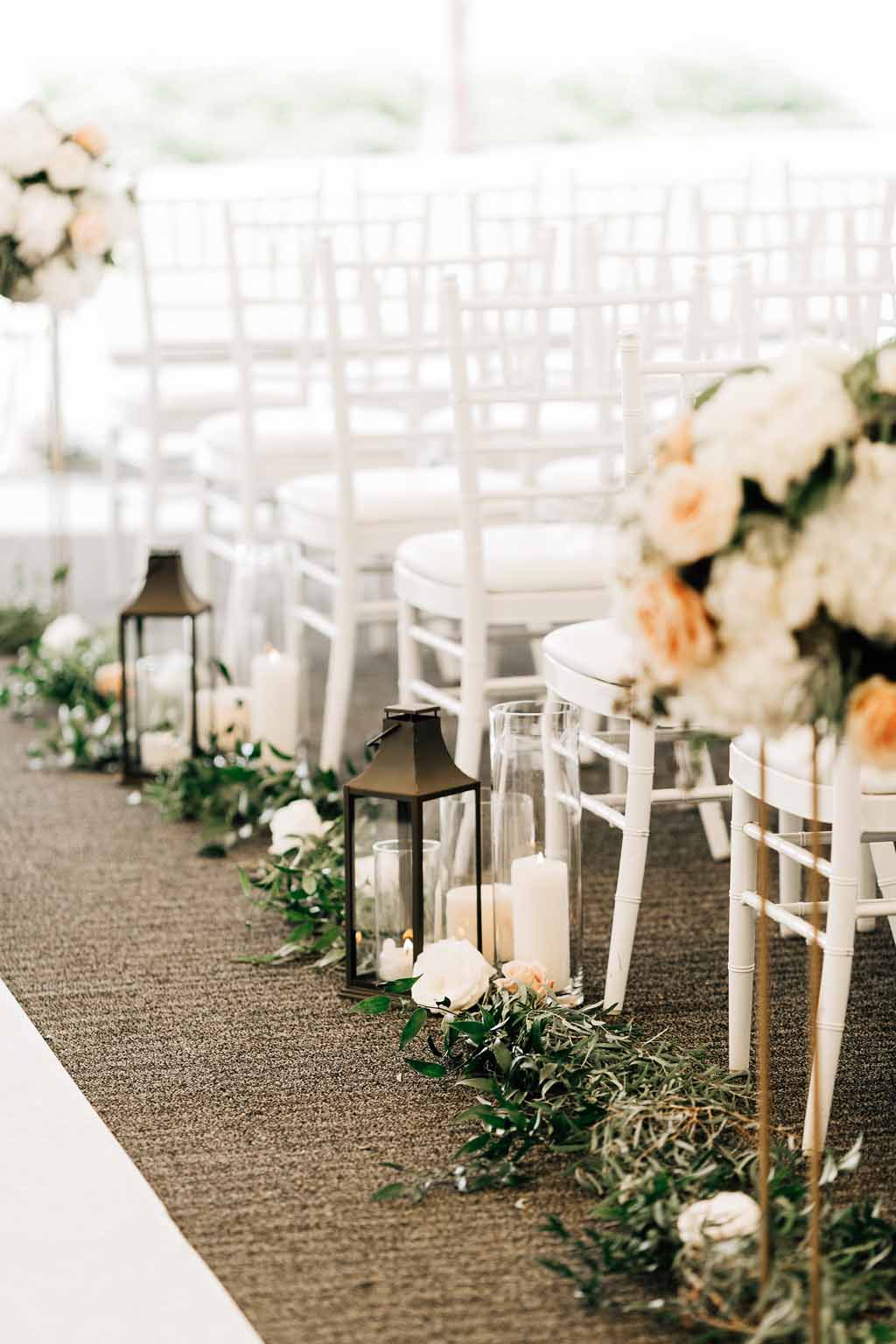 Wedding ceremony aisle lined with ivory and peach spring flowers, greenery, and lanterns, with white Chivari chairs