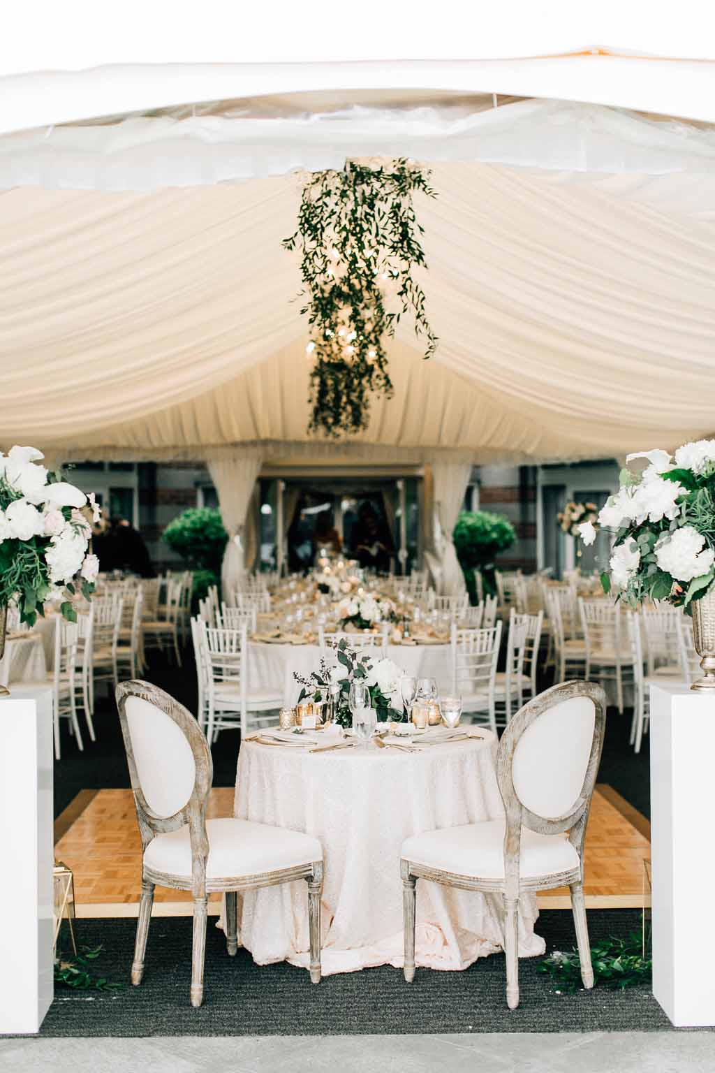 Sweetheart table at Woodmark Hotel wedding with greenery chandeliers, and tall floral backdrop on top of white pedestals