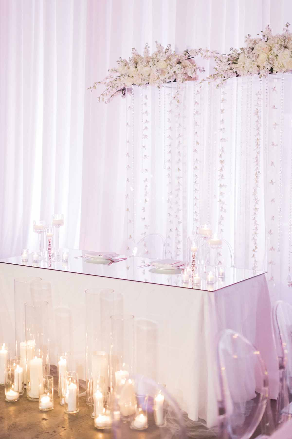 all white head table with wedding arch background