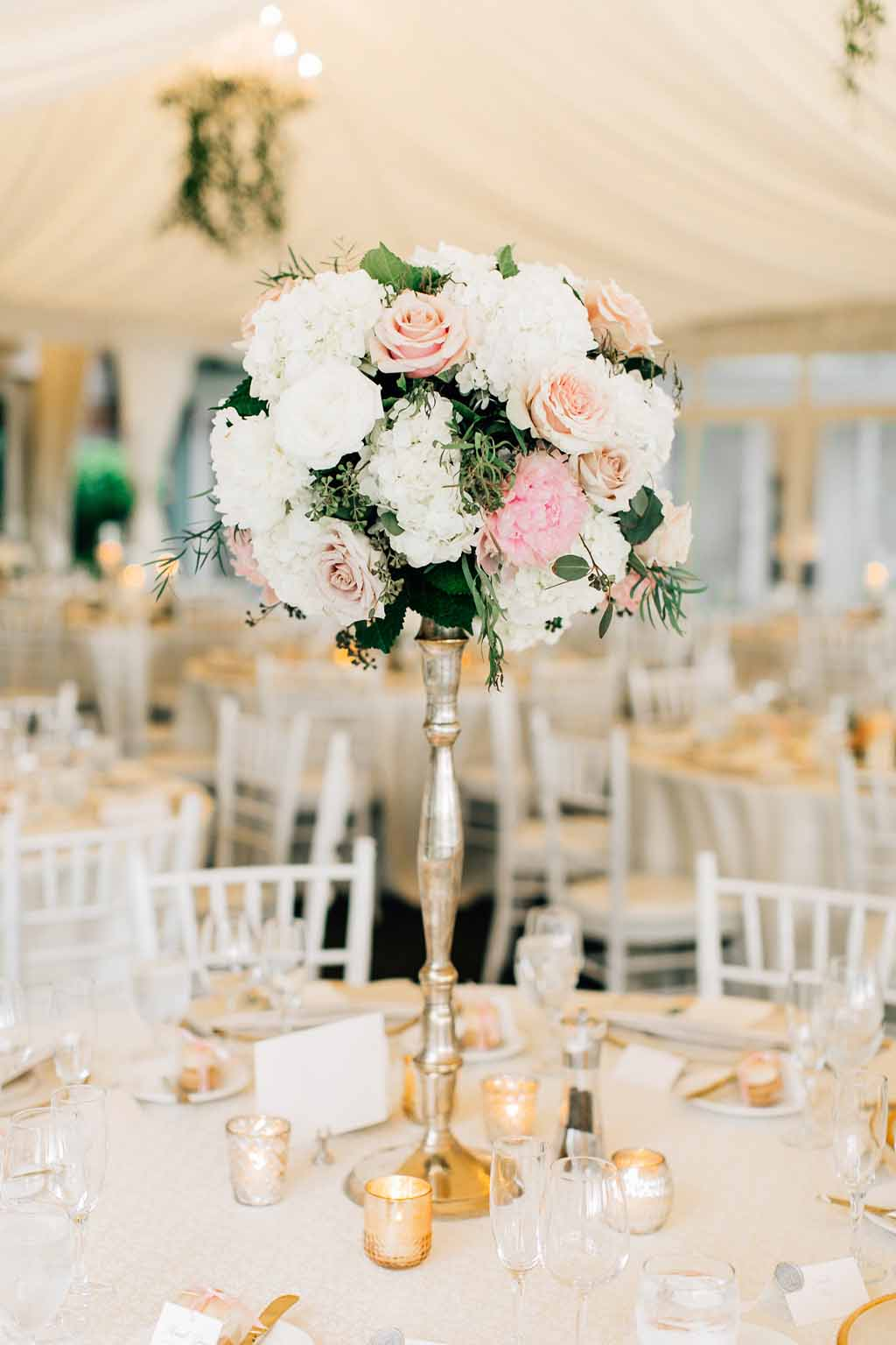 Elevated centerpiece on top of a silver vintage stand featuring peach roses, white hydrangea, white peonies, and greenery