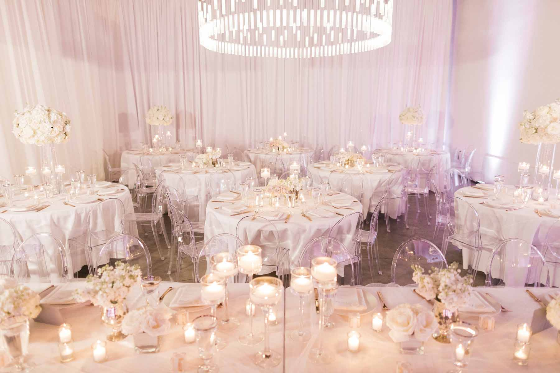 All white wedding reception at Canvas Event Space Seattle with white draping, white table linens, floating candles, white flower centerpieces