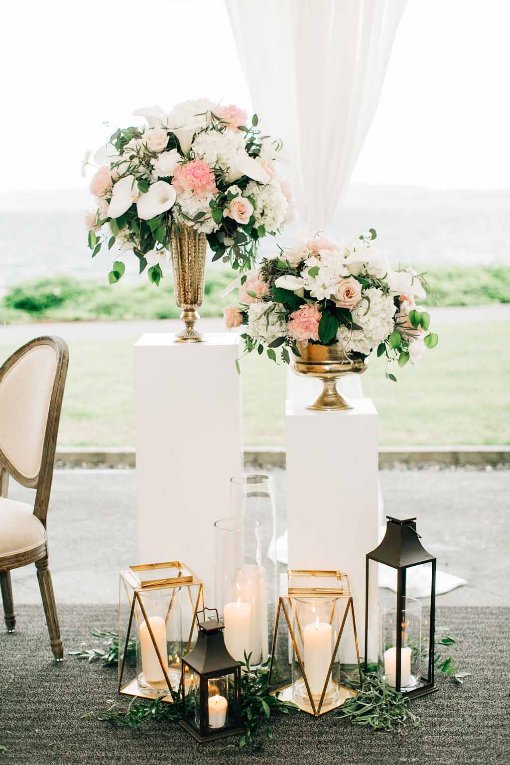 Sweetheart table with gorgeous backdrop of tall floral pieces looking over Lake Washington
