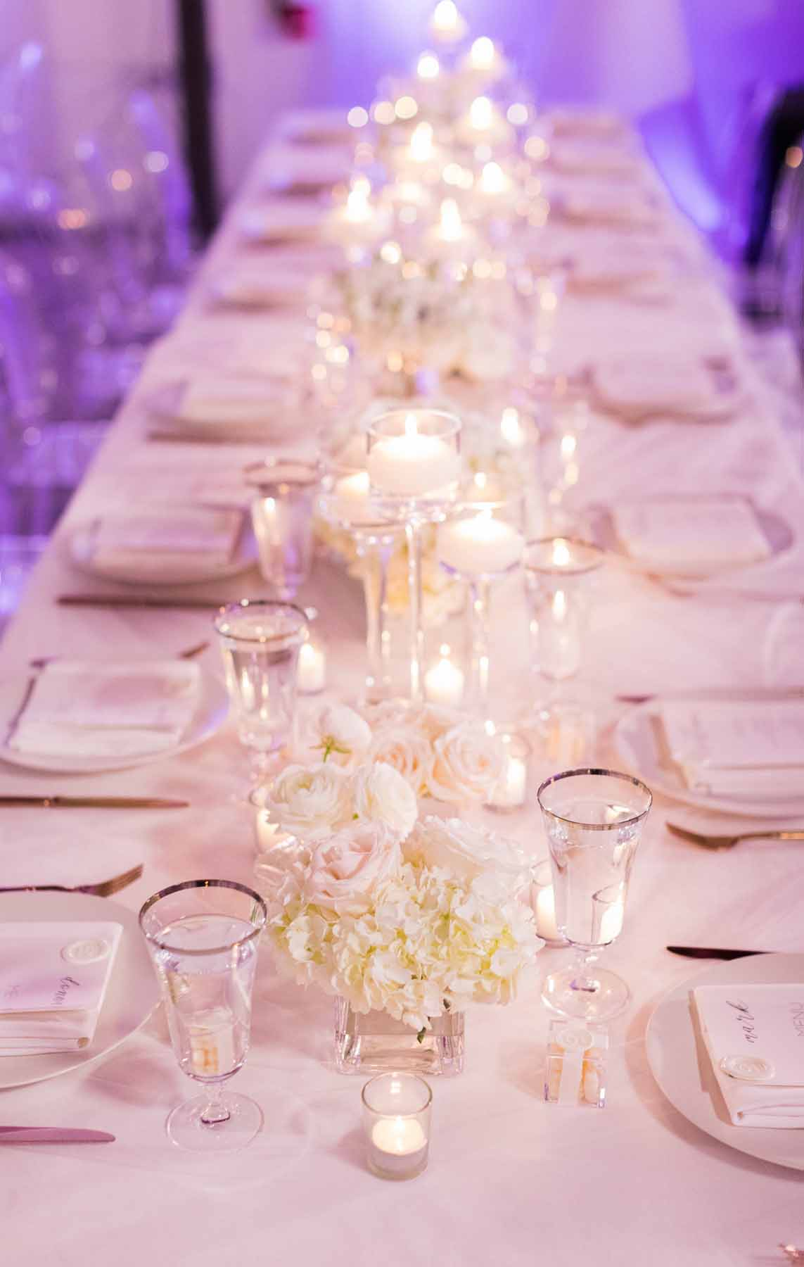 Long wedding reception table lined with white flowers and candles - Flora Nova Design