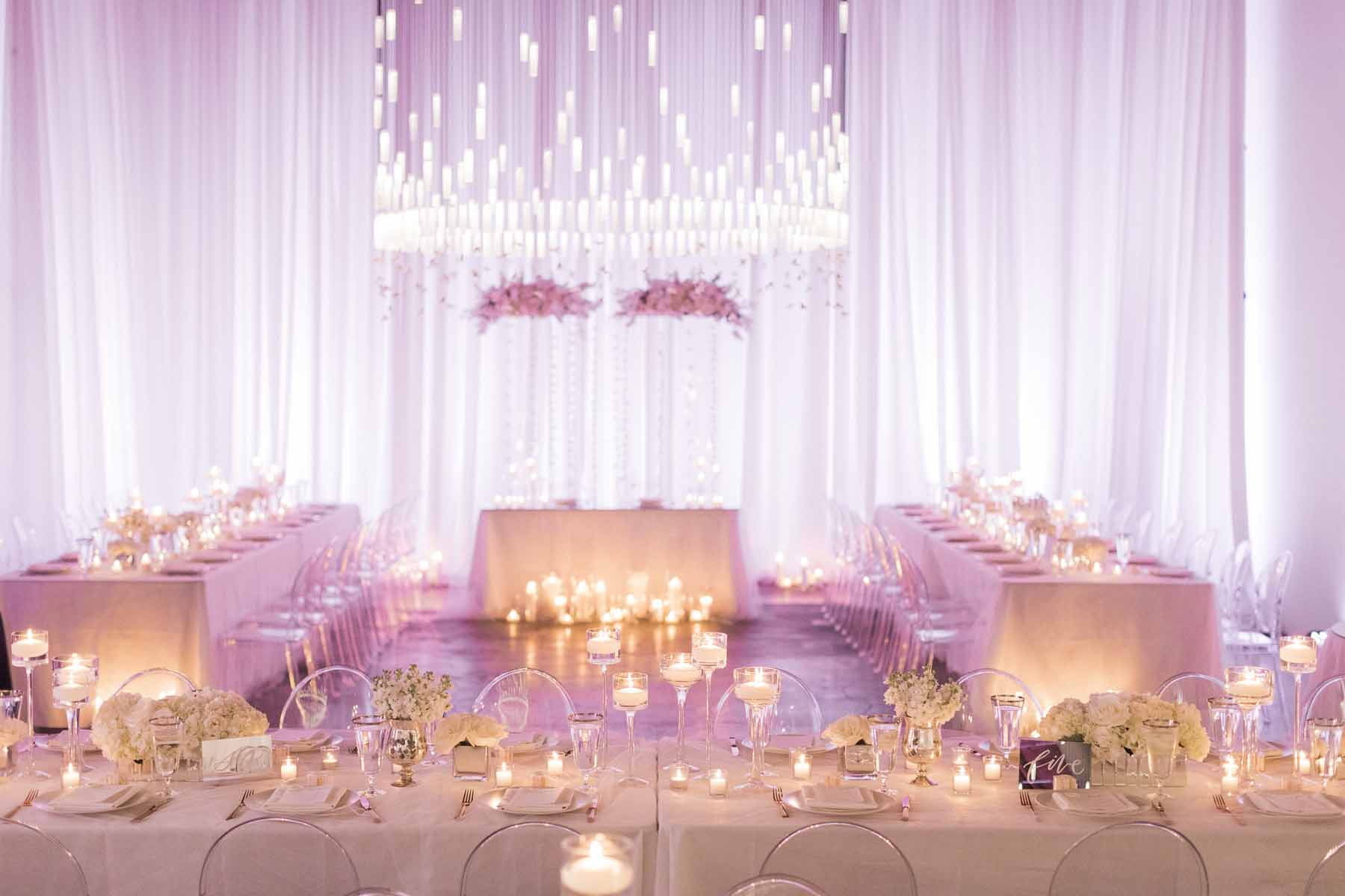 Beautiful reception at Canvas Event Space wedding with white draping, white tables, lots of candles under a large crystal chandeliers