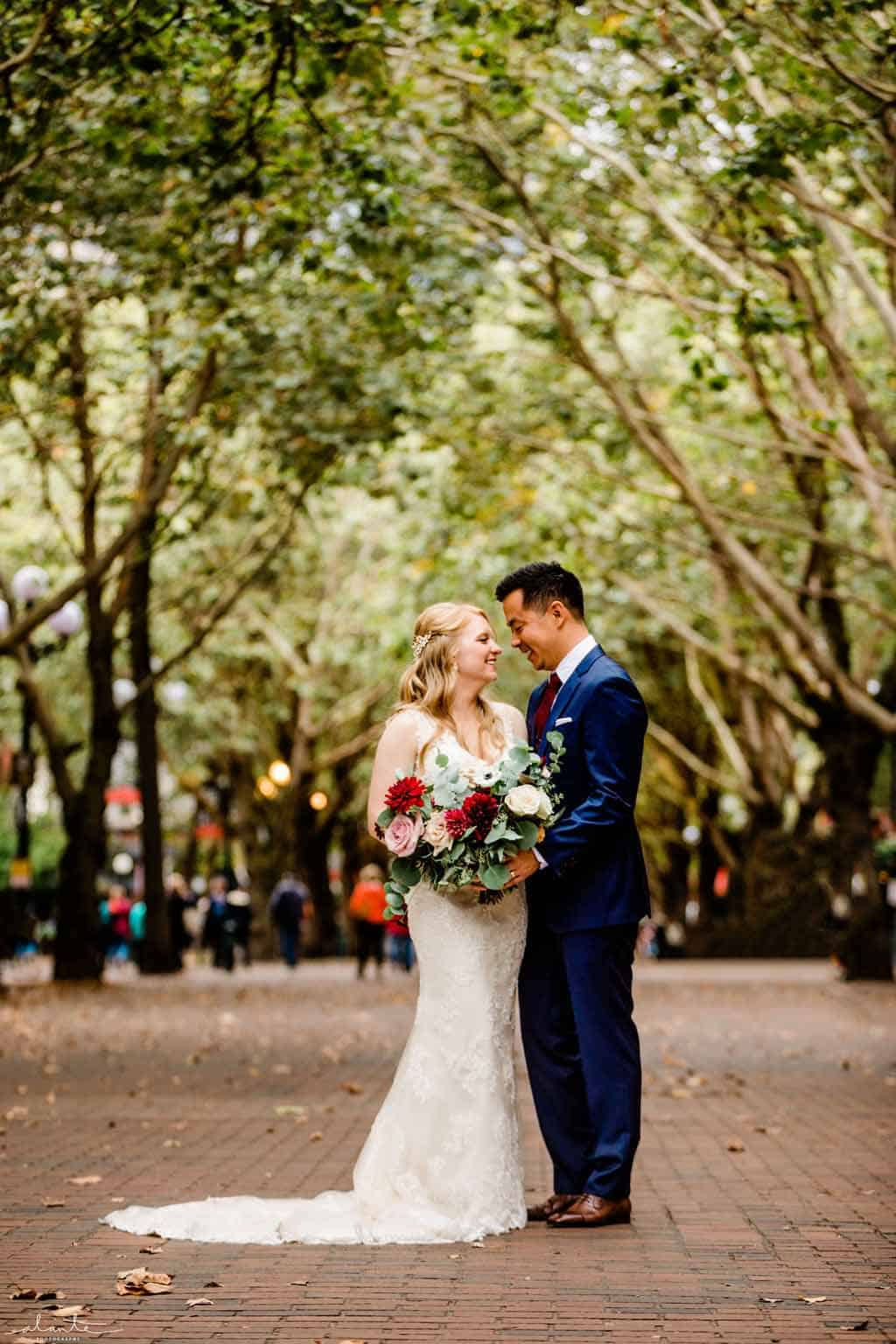 Bride and groom posing under tall trees with wedding bouquet