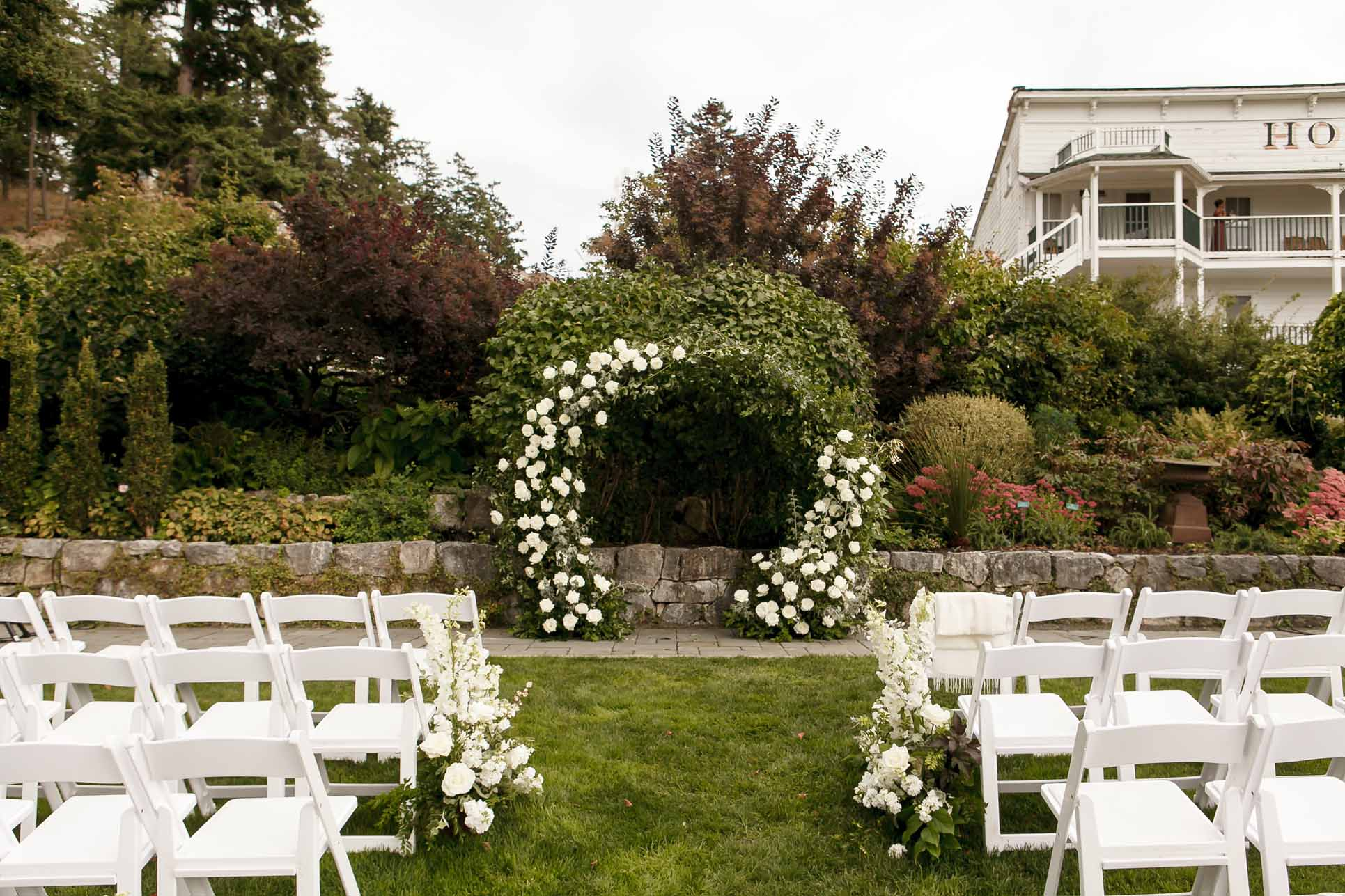 Outdoor wedding ceremony at Roche Harbor, with white flower arch